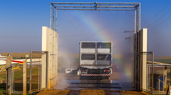 a imagem mostra um caminhão sendo desinfectado para entrar na granja, por conta das medidas de biossegurança